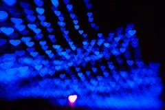 Il bello bokeh fatto del blu caldo ha offuscato le luci sotto forma di cuori Immagine Stock Libera da Diritti