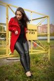 Il bello cappotto della ragazza in rosso è basato sul recinto fotografie stock libere da diritti