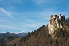Il bello castello ha sanguinato sopra la collina sopra il lago con le alpi julian nella parte posteriore Fotografia Stock