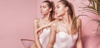 Il bello caucasian gemella i modelli femminili su fondo rosa Immagini Stock
