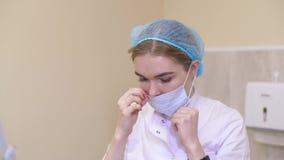 Il bello chirurgo della donna mette sopra una maschera e prepara per chirurgia Giovane infermiere che mette sulla maschera stock footage