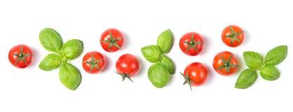Il bello confine ha fatto dei pomodori ciliegia freschi con le foglie del basilico, isolato su fondo bianco, modello di verdure,  immagine stock