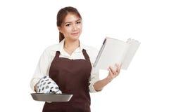 Il bello cuoco asiatico della ragazza con la padella ha letto il libro del cuoco Fotografia Stock