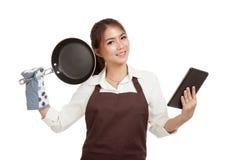 Il bello cuoco asiatico della ragazza con la padella ha letto il pc della compressa Fotografie Stock Libere da Diritti