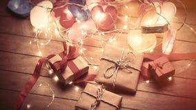 Il bello cuore variopinto ha modellato la ghirlanda ed i regali svegli che si trovano sopra Fotografia Stock Libera da Diritti
