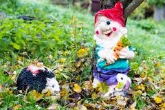 Il bello e gnomo variopinto del giardino con un piccolo istrice sta stando sotto un albero Foglie d'ingiallimento dall'albero fotografie stock libere da diritti