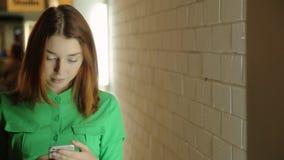 Il bello e la giovane donna stanno fermandosi nel corridoio che manda un sms, scrivente o componente al numero a macchin'in cellu stock footage