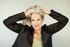 Il bello e meglio sicuro di sé sbalorditivo ha invecchiato la donna con capelli grigi che sorride nella macchina fotografica immagine stock