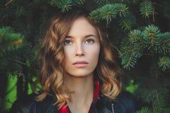 Il bello fronte di una giovane donna sorridente contro un fondo di abete si ramifica Fotografia Stock