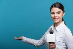 Il bello giornalista della ragazza TV con il sorriso grazioso è fotografia stock libera da diritti