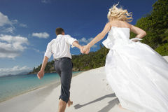 Il bello giovane funzionamento delle coppie sul tramonto, camminante a piedi nudi su è Fotografie Stock Libere da Diritti
