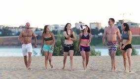 Il bello giovane mette in mostra gli uomini e le donne che camminano sulla spiaggia dopo un gioco di pallavolo, parlando, sorride archivi video