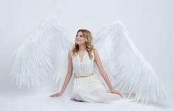 Il bello giovane modello con il grande angelo traversa la seduta volando nello studio Immagini Stock