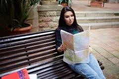Il bello giovane studio dello studente su una mappa trova l'itinerario giusto Immagine Stock