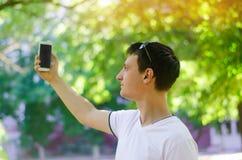 Il bello giovane tipo europeo che prende le immagini se stesso e fa il selfie in una città parcheggiare all'aperto stile di vita, fotografie stock libere da diritti