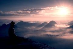 Il bello giovane turista lungo della ragazza dei capelli gode dell'alba sull'angolo tagliente della roccia dell'arenaria e guarda Immagini Stock