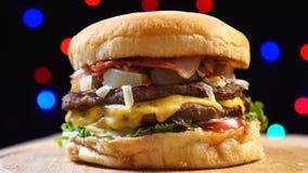 Il bello hamburger cucinato succoso fresco fresco gira sulla piattaforma girevole contro un fondo delle luci confuse variopinte archivi video