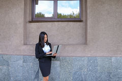 Il bello imprenditore della ragazza tiene il computer portatile e gli impianti, risolve Immagini Stock Libere da Diritti