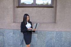 Il bello imprenditore della ragazza tiene il computer portatile e gli impianti, risolve Fotografia Stock
