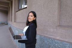 Il bello imprenditore della ragazza tiene il computer portatile e gli impianti, risolve Fotografia Stock Libera da Diritti