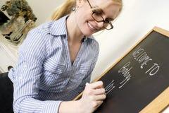 L'insegnante scrive un messaggio sulla lavagna che dice il benvenuto a biologia immagini stock libere da diritti