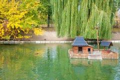 Il bello lago con le piccole case di legno per le anatre e gli alberi di autunno in città parcheggiano Immagine Stock