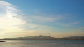 Il bello lago e la barca bianca galleggia nella distanza stock footage