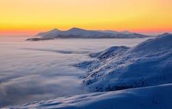 Il bello lustro del tramonto chiarisce i paesaggi pittoreschi con gli alberi giusti coperti di neve e di alte montagne Immagini Stock