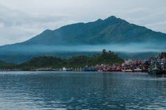 Il bello mare blu, il villaggio del pescatore sulla costa ed hanno grande moun Fotografia Stock Libera da Diritti