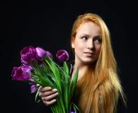 Il bello mazzo redheaded della tenuta della ragazza dei tulipani porpora fiorisce Immagine Stock