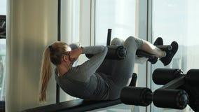 Il bello mezzo sportivo ha invecchiato la donna che fa gli esercizi per gli ABS archivi video
