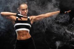 Il bello modello afroamericano sportivo, donna in sportwear fa la forma fisica che si esercita al fondo nero per restare adatto fotografia stock libera da diritti