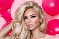 Il bello modello della donna con capelli biondi lunghi si è vestito in un vestito rosa che sta su un fondo rosa Fotografie Stock Libere da Diritti