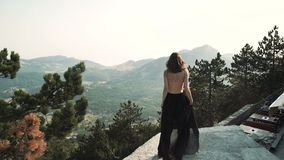 Il bello modello della giovane donna con capelli lunghi in un vestito lungo elegante lanuginoso nero sta camminando lungo il balc archivi video