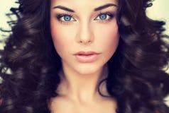 Il bello modello della ragazza del ritratto con il nero lungo ha arricciato i capelli fotografie stock