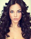 Il bello modello della ragazza del ritratto con il nero lungo ha arricciato i capelli immagini stock libere da diritti