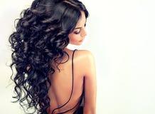 Il bello modello della ragazza del ritratto con il nero lungo ha arricciato i capelli Fotografia Stock