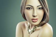 Il bello modello di moda con trucco e gioielli sta esaminando la macchina fotografica Fondo verde, colpo dello studio Sviluppato  Fotografia Stock