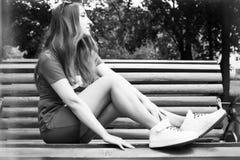 Il bello modello si siede su un banco nel parco Fotografie Stock
