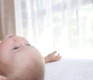 Il neonato è trovantesi e guardante su Fotografia Stock