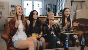 Il bello orologio TV delle amiche, celebra il successo Le ragazze abbastanza emozionali dei giovani ridono il movimento lento di  immagine stock libera da diritti