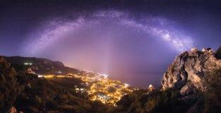 Il bello paesaggio di notte con la Via Lattea contro la città si accende fotografia stock libera da diritti