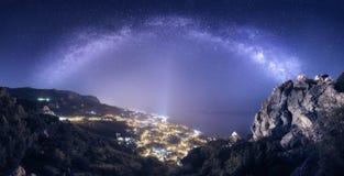 Il bello paesaggio di notte con la Via Lattea contro la città si accende immagine stock