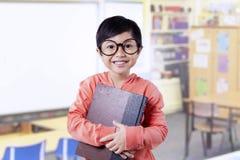 Il bello piccolo studente tiene i libri nella classe Immagine Stock