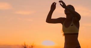 Il bello primo piano sexy del giocatore di pallavolo della donna in bikini al tramonto sulla spiaggia dà il passaggio superiore archivi video