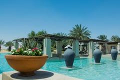 Il bello punto di vista della piscina con le palme, le brocche ed i fiori al deserto arabo di lusso ricorrono Fotografia Stock Libera da Diritti