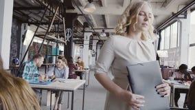 Il bello responsabile femminile biondo cammina attraverso l'ufficio, controlla il lavoro all'ufficio, la direzione di elasticità  stock footage