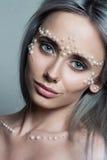 Il bello ritratto della giovane donna con i gioielli della perla e compone Fotografia Stock Libera da Diritti