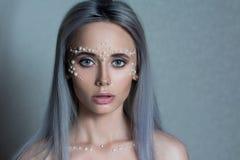 Il bello ritratto della giovane donna con i gioielli della perla e compone Fotografie Stock