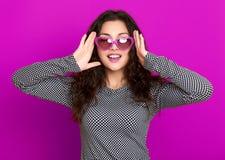 Il bello ritratto della giovane donna, posante sul fondo porpora, capelli ricci lunghi, occhiali da sole nel cuore modella, conce Immagine Stock